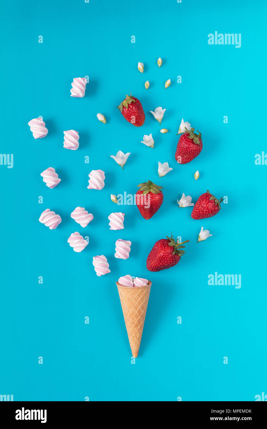 Waffle cone with marshmallows, fresh strawberries and flowers jasmine blossom bouquets on blue surface. Flat lay, top view sweet food floral backgroun - Stock Image