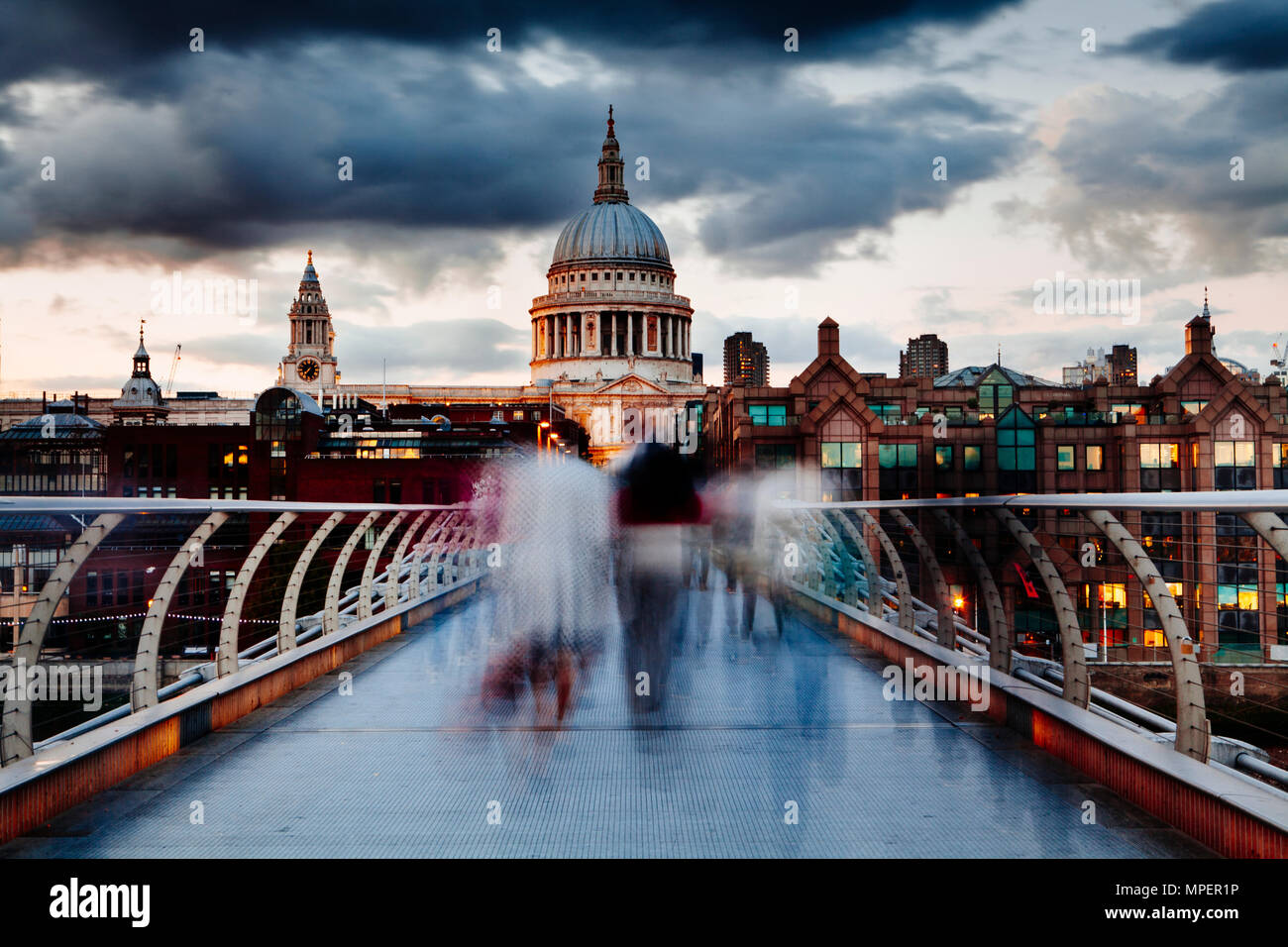 Early evening on London's Millennium Bridge with people crossing in motion blur and a view of St Pauls Cathedral. - Stock Image