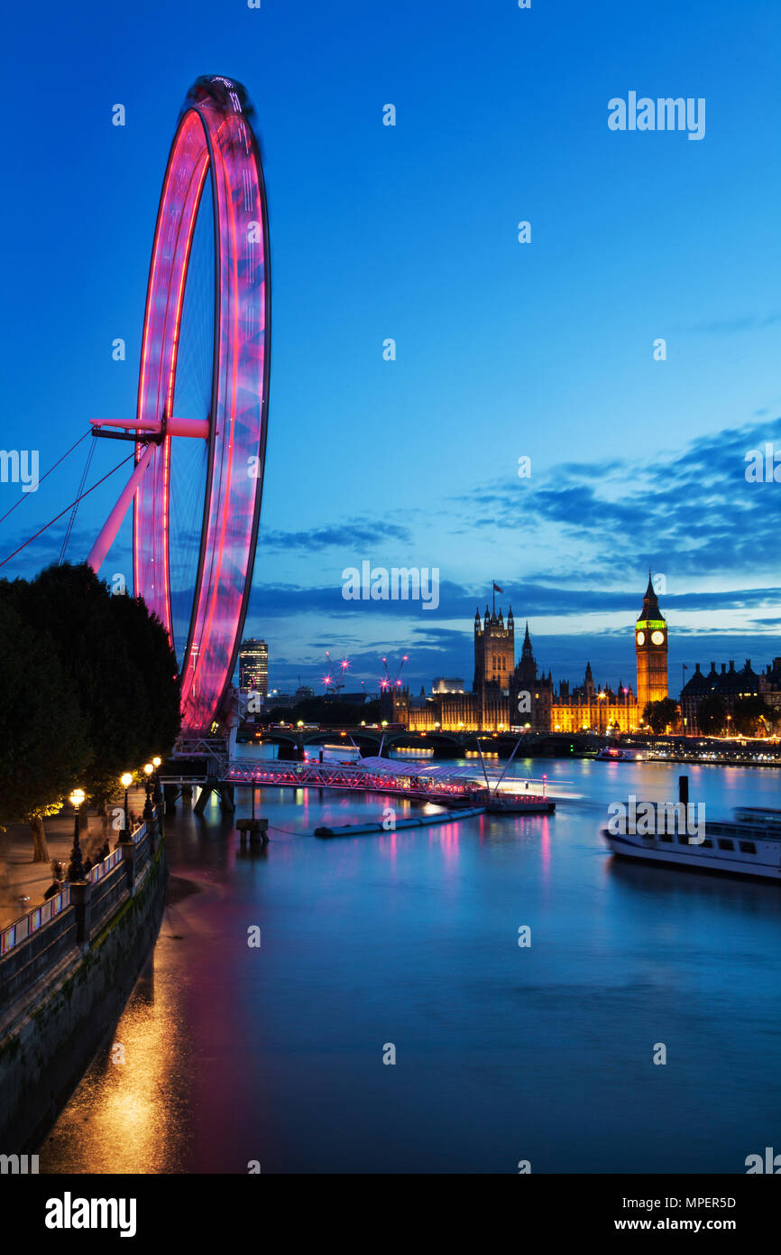 LONDON - September 13, 2015: View of London Eye at night with Thames river in London, England. London Eye is a famous tourist attraction at a height o - Stock Image