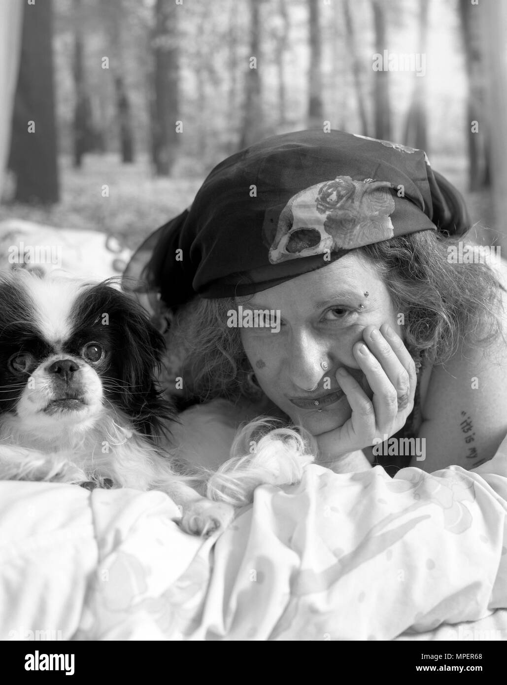 Woman in bed with her Japanese Chin dog. - Stock Image