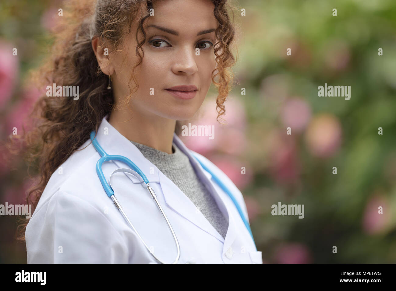 Portrait of a young woman, doctor, physician, medical practitioner in lab coat in natural outdoor settings - Stock Image