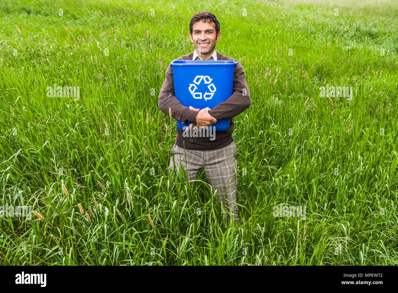 A man standing in a field of green grass and trees holding a recycle bin. A positive conceptual shot of recycling. - Stock Image