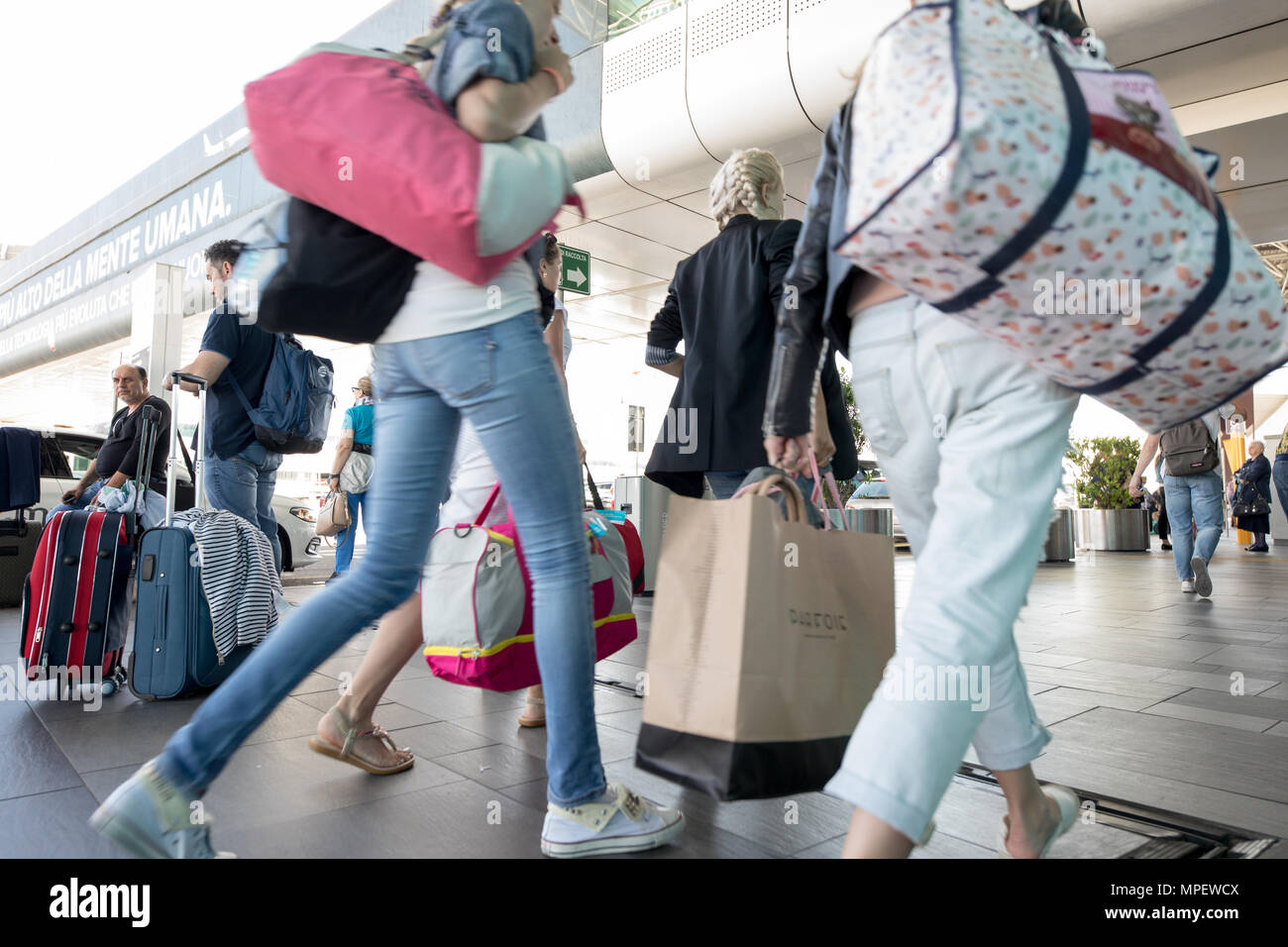 Rome Fiumicino airport, passengers walking with trolley and suitcase - Stock Image