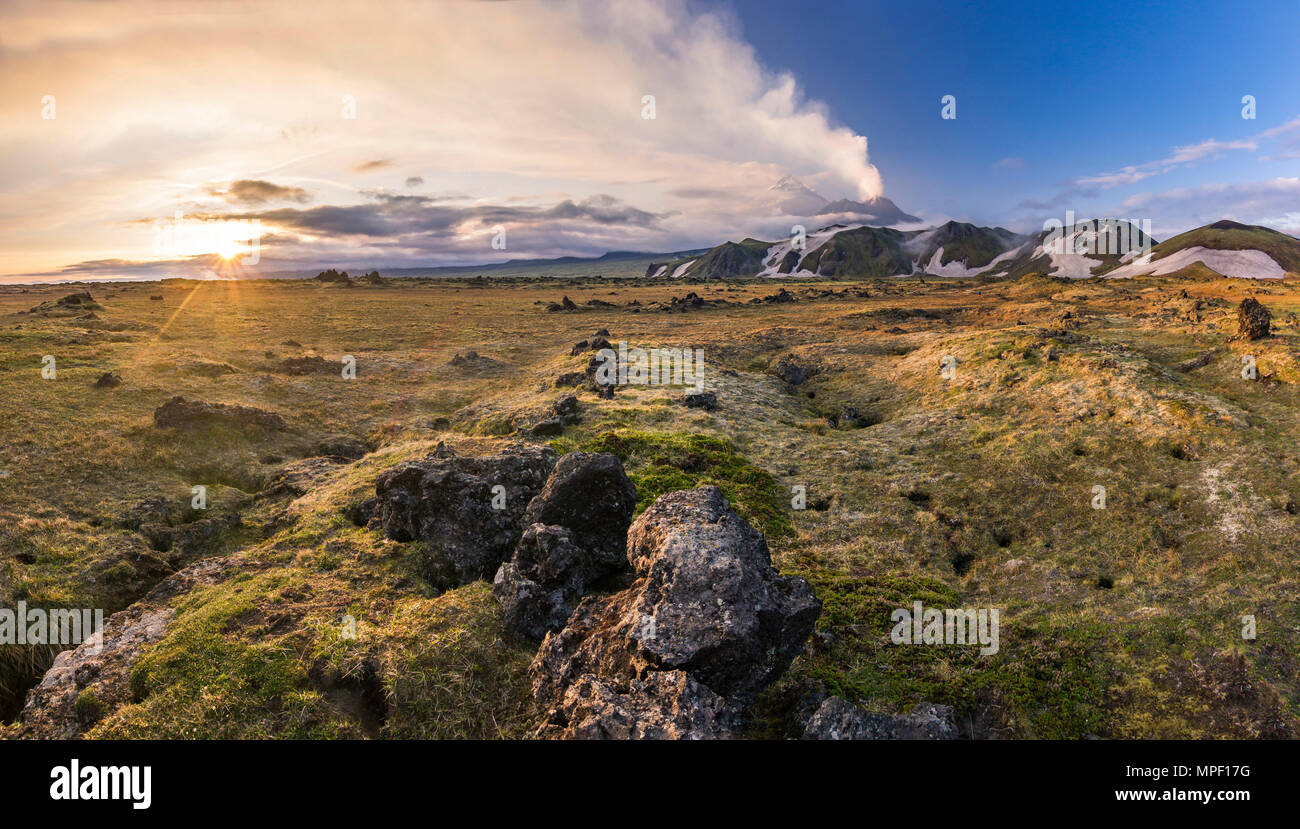 active volcanoes of Kamchatka with snowy hills at sunset - Stock Image