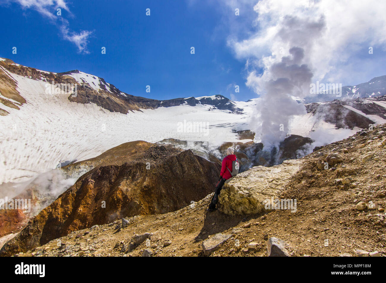 girl sitting near steaming crater of active volcano covered by snow - Stock Image