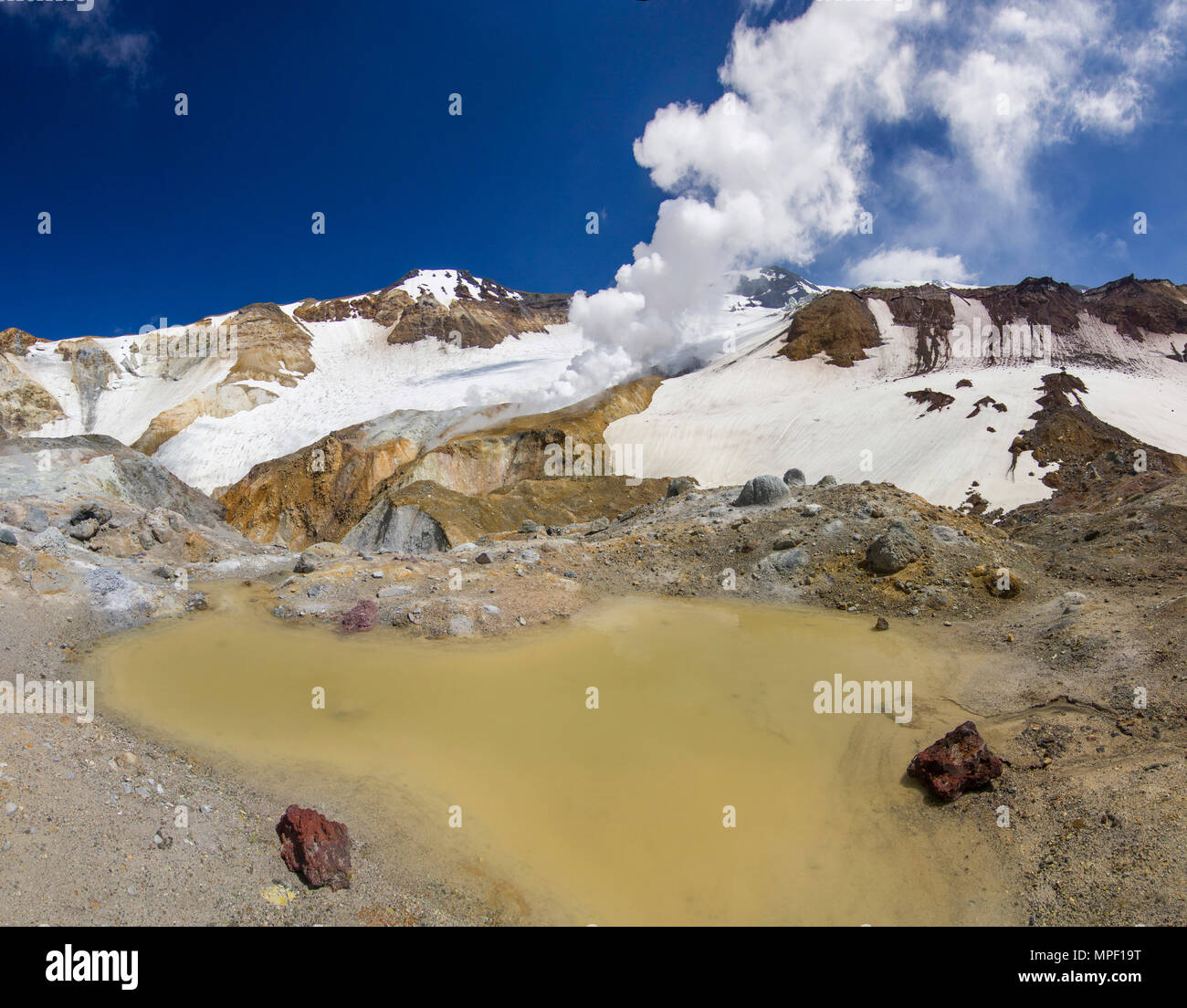 steaming crater of active volcano covered by snow - Stock Image