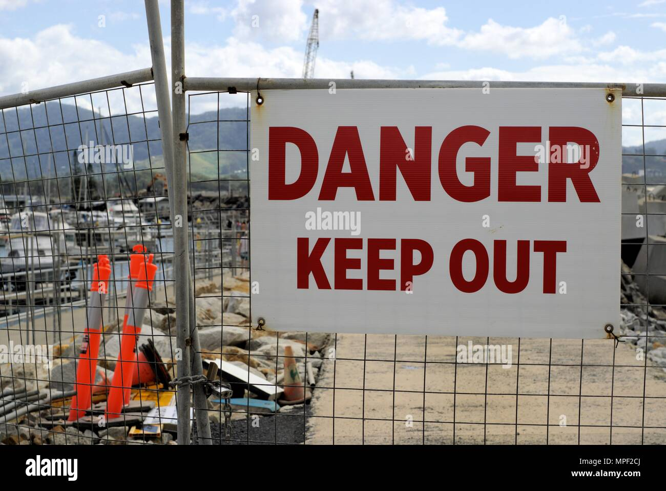 'Danger Keep Out' sign board on fence gate at construction site in Australia - Stock Image