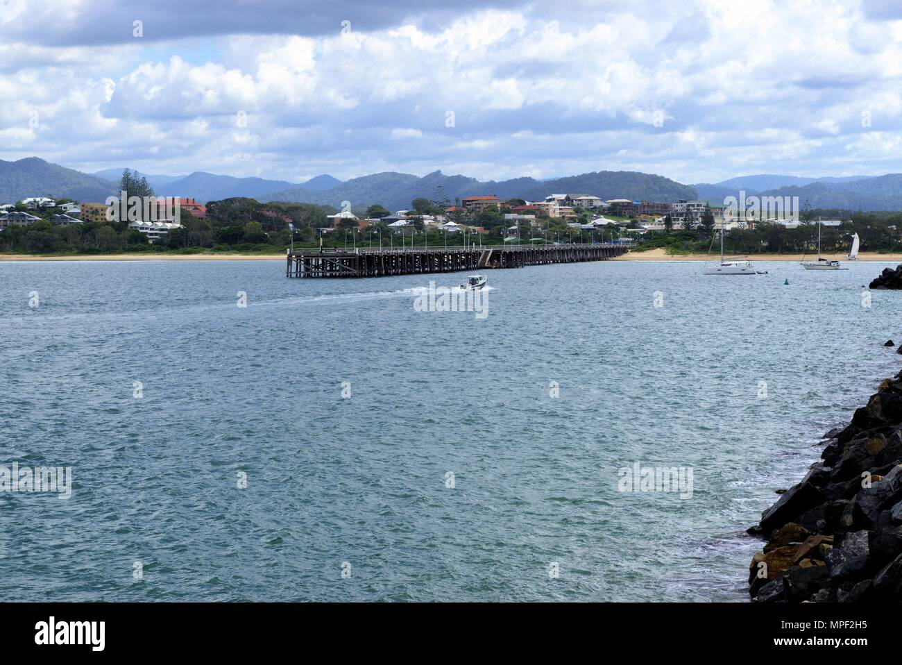 21 April 2018. Speed boat in water going towards jetty at Jetty Beach in Australian city of Coffs Harbour. Wide view of jetty in Australia. - Stock Image