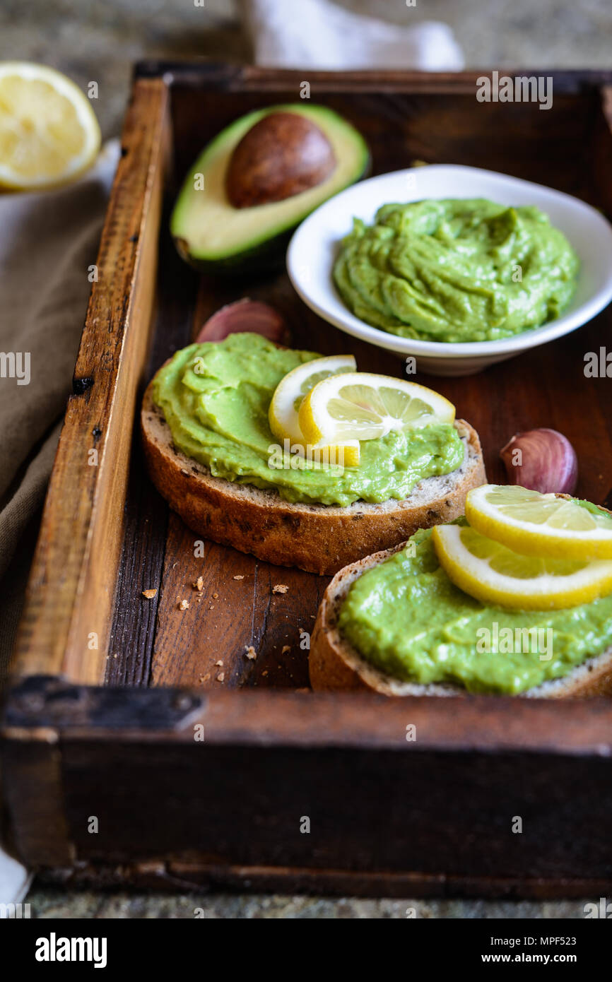 Healthy avocado spread with garlic on wholewheat slice of bread - Stock Image