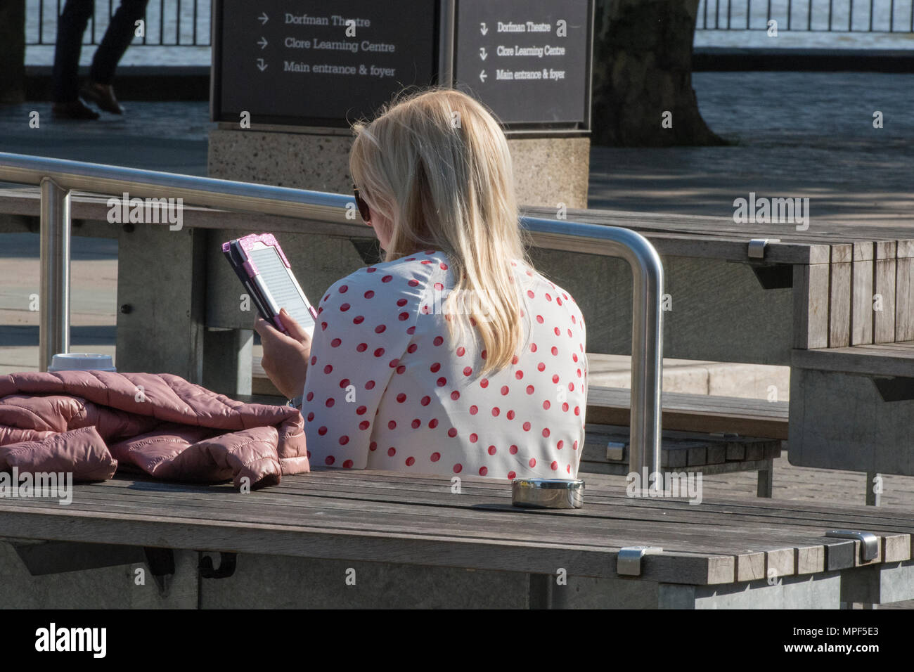 A young woman sitting down outside of the royal festival hall and national theatre in London relaxing and using an iPad in the warm summer sunshine. - Stock Image