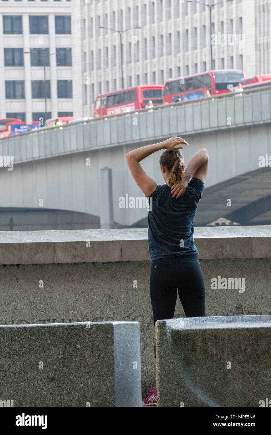 a young woman taking exercise or exercising during the morning rush hour in central London. stretching exercises to loosen up muscles after running. - Stock Image