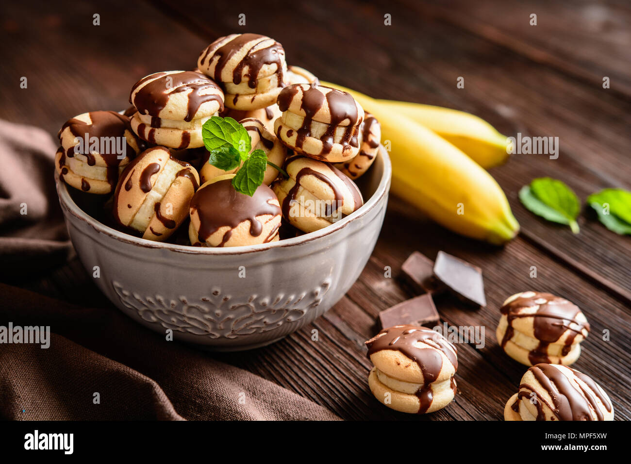 Round sponge biscuits stuffed with banana slices and topped with chocolate - Stock Image