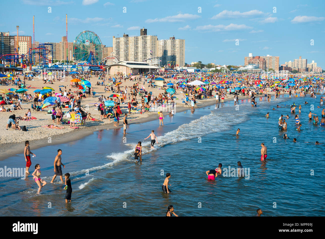 NEW YORK CITY - AUGUST 20, 2017: View of people enjoying a summer's day on crowded Coney Island beach and boardwalk. - Stock Image