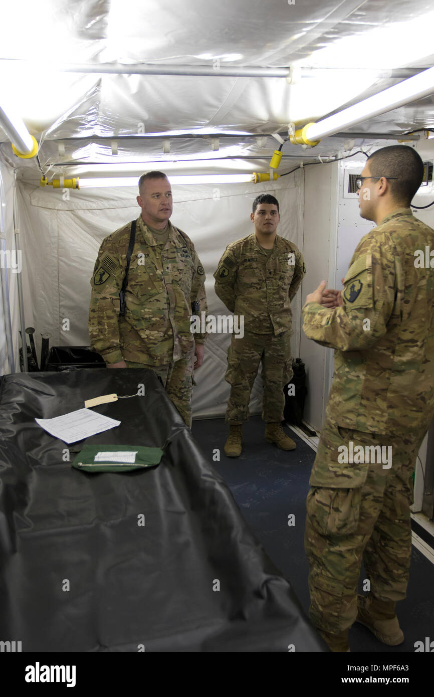 Spc. Jose Perez, a mortuary affairs specialist with the 246th Quartermaster Company (Mortuary Affairs), an U.S. Army Reserve unit based out of Mayaguez, Puerto Rico, (right), explains the capabilities of a Mobile Integrated Remains Collections System (MIRCS) to Brig. Gen. Robert D. Harter, deputy commanding general of the 1st Sustainment Command (Theater) / commanding general of the 316th Sustainment Command (Expeditionary), (left), in Erbil, Iraq on February 3, 2017. (U.S. Army photo by Staff Sgt. Dalton Smith) - Stock Image