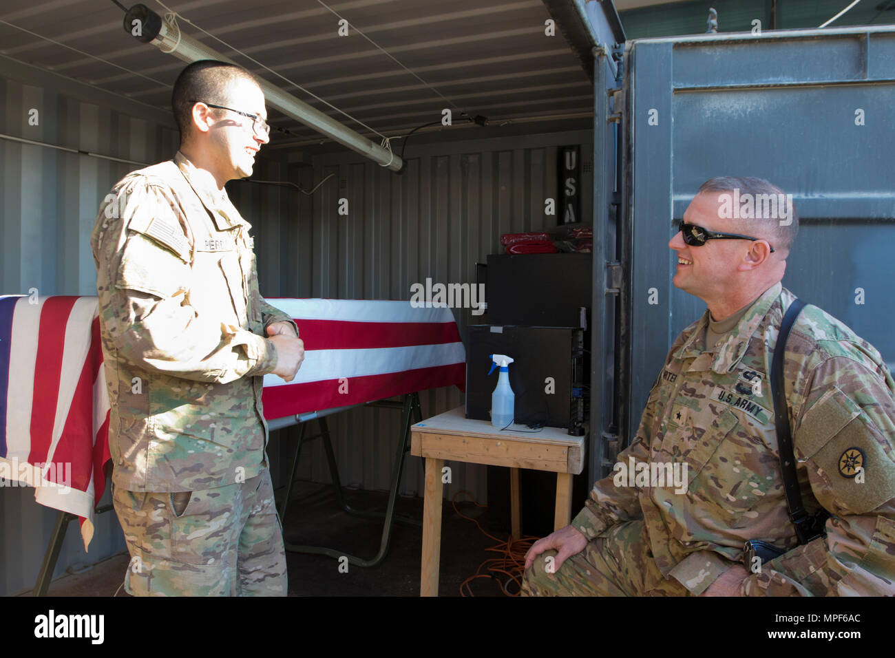 Spc. Jose Perez, a mortuary affairs specialist with the 246th Quartermaster Company (Mortuary Affairs), an U.S. Army Reserve unit based out of Mayaguez, Puerto Rico, (left), explains the capabilities of a Mobile Integrated Remains Collections System (MIRCS) to Brig. Gen. Robert D. Harter, deputy commanding general of the 1st Sustainment Command (Theater) / commanding general of the 316th Sustainment Command (Expeditionary), (right), in Erbil, Iraq on February 3, 2017. (U.S. Army photo by Staff Sgt. Dalton Smith) - Stock Image