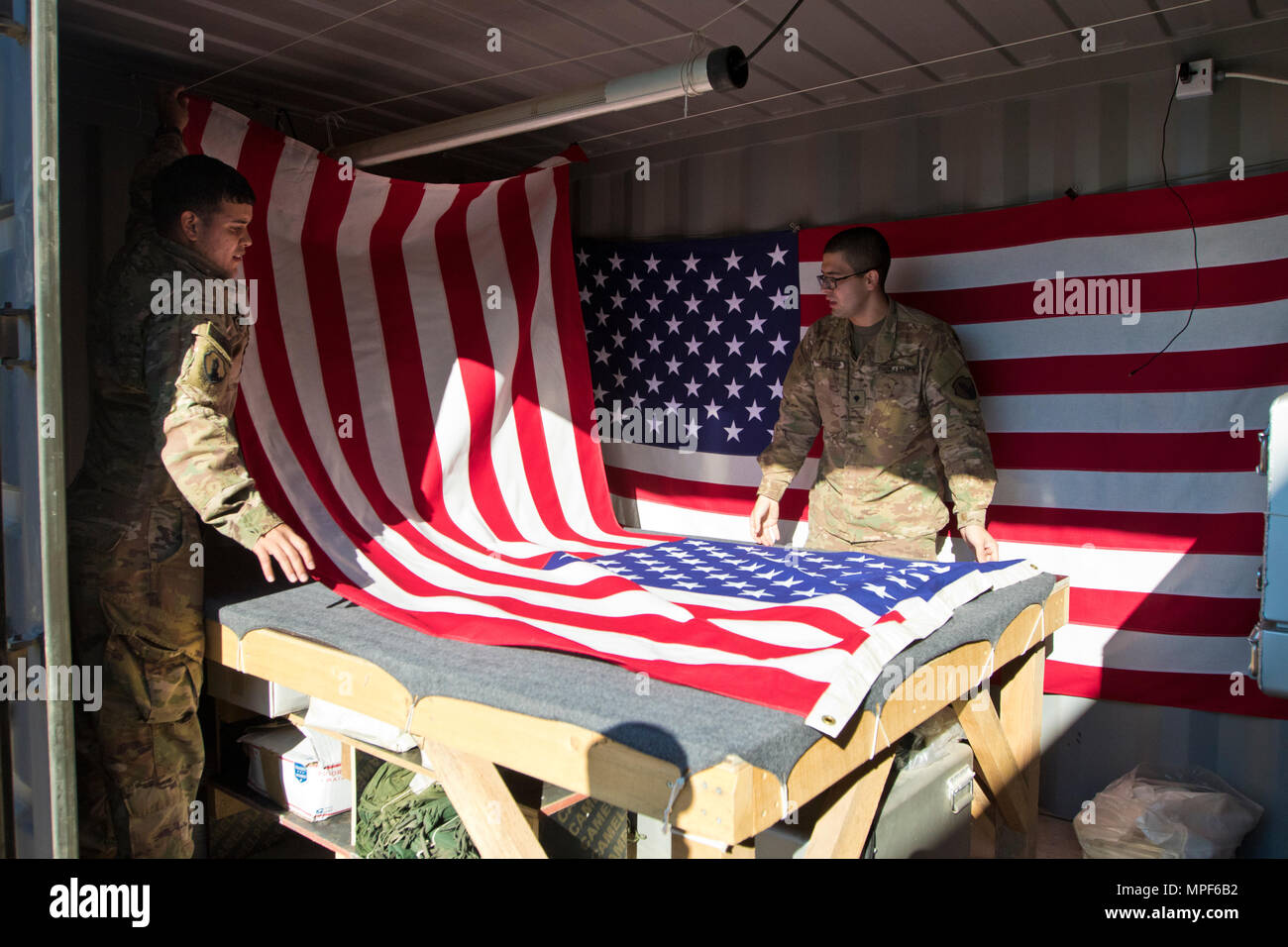 Spc. Brian Ramirez, (left), and Spc. Jose Perez, (right), both mortuary affairs specialists with the 246th Quartermaster Company (Mortuary Affairs), an U.S. Army Reserve unit based out of Mayaguez, Puerto Rico, drapes an American Flag over a transfer case in Erbil, Iraq on February 3, 2017. (U.S. Army photo by Staff Sgt. Dalton Smith) - Stock Image