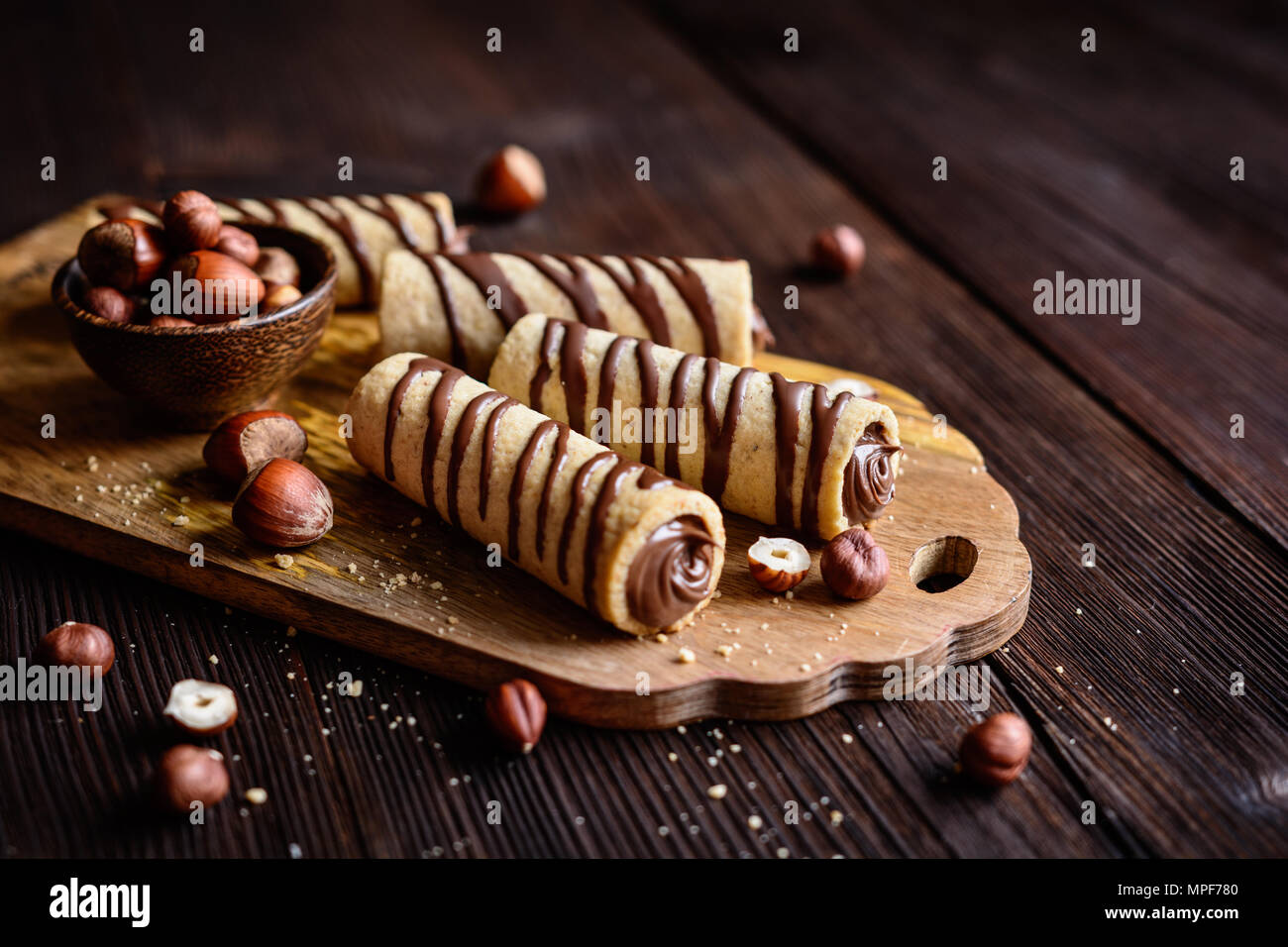 Delicious biscuit tubes filled with hazelnut cream and chocolate topping - Stock Image
