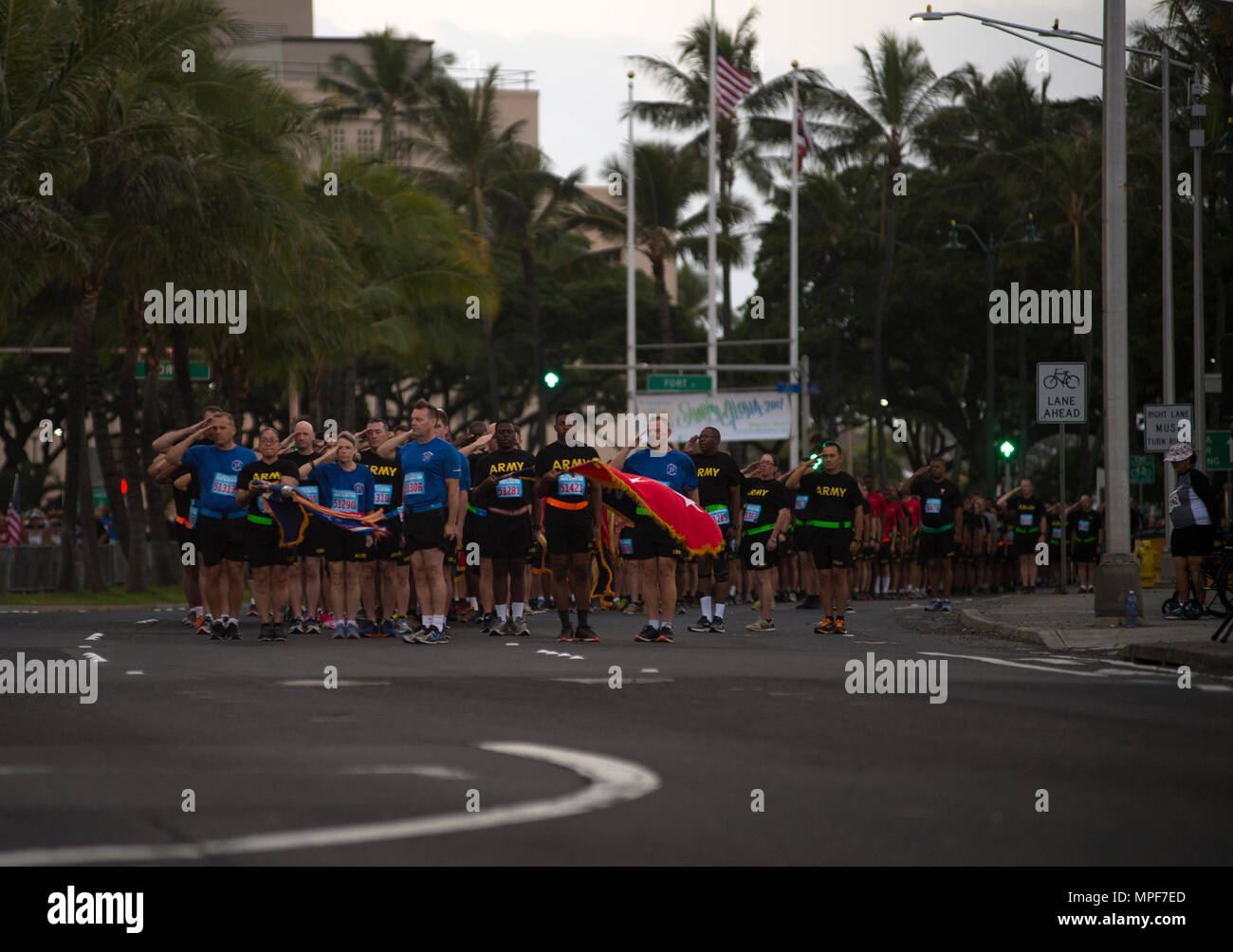 "170220-N-WC566-004 HONOLULU (Feb. 20, 2017)   Service members, representing the 'Sounds of Freedom' team, salute during the National Anthem before the Great Aloha Run, held in Honolulu, Feb. 20. The ""Sounds of Freedom"" team runs in a formation with their unit, consisting of service men and women from all branches of service. The Great Aloha Run is 8.15 miles and is an annual charity event. A portion of the proceeds benefits local military assistance programs. (U.S. Navy photo by Mass Communication Specialist 2nd Class Gabrielle Joyner/Released) - Stock Image"