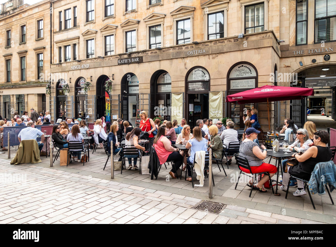 People drinking and chatting at open-air tables in John Street in the Merchant City area of Glasgow, Scotland, UK - Stock Image