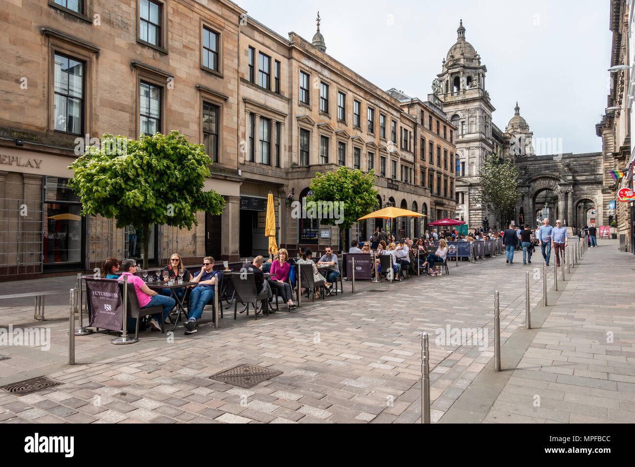 John Street in the Merchant City of Glasgow, on a warm May evening, with people walking and others eating and drinking. Scotland, UK - Stock Image