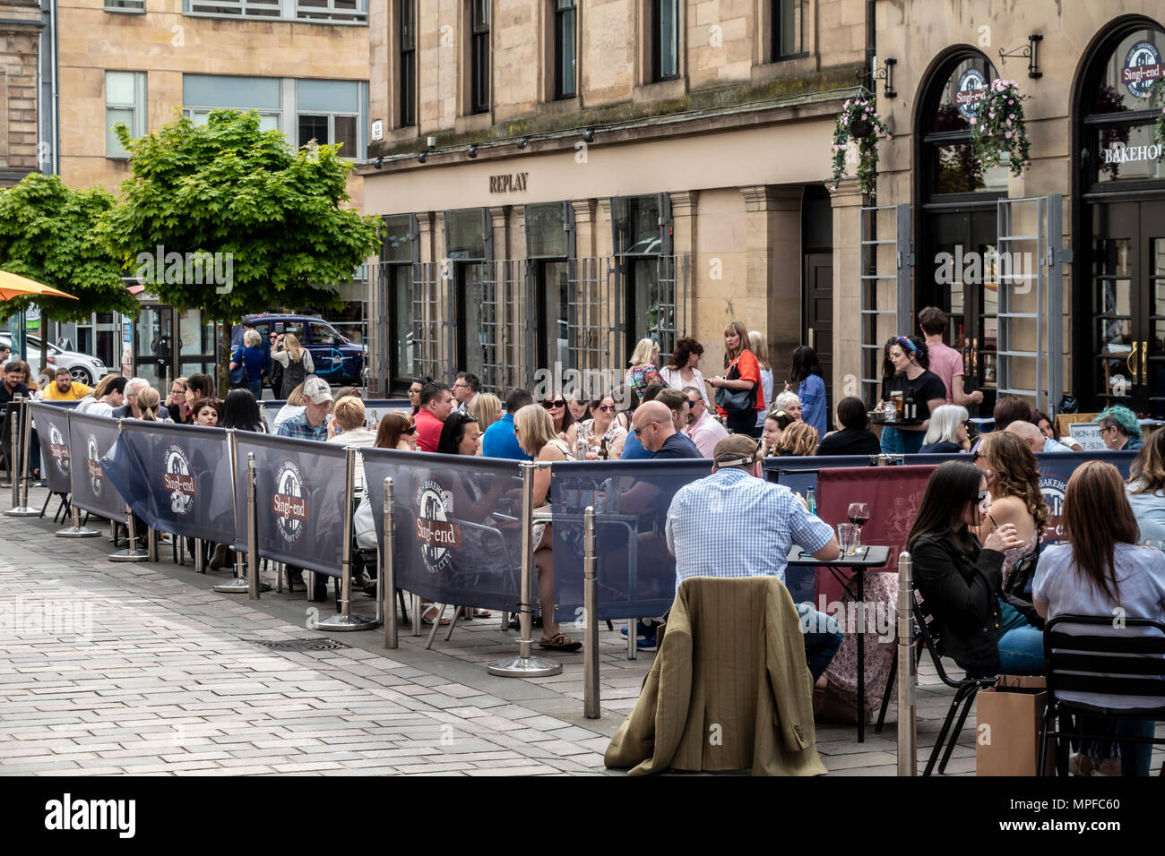 Large group of people in the outdoor seated area of the Singl-end Bakehouse & cafe, John St, Merchant City, Glasgow, Scotland, UK - Stock Image