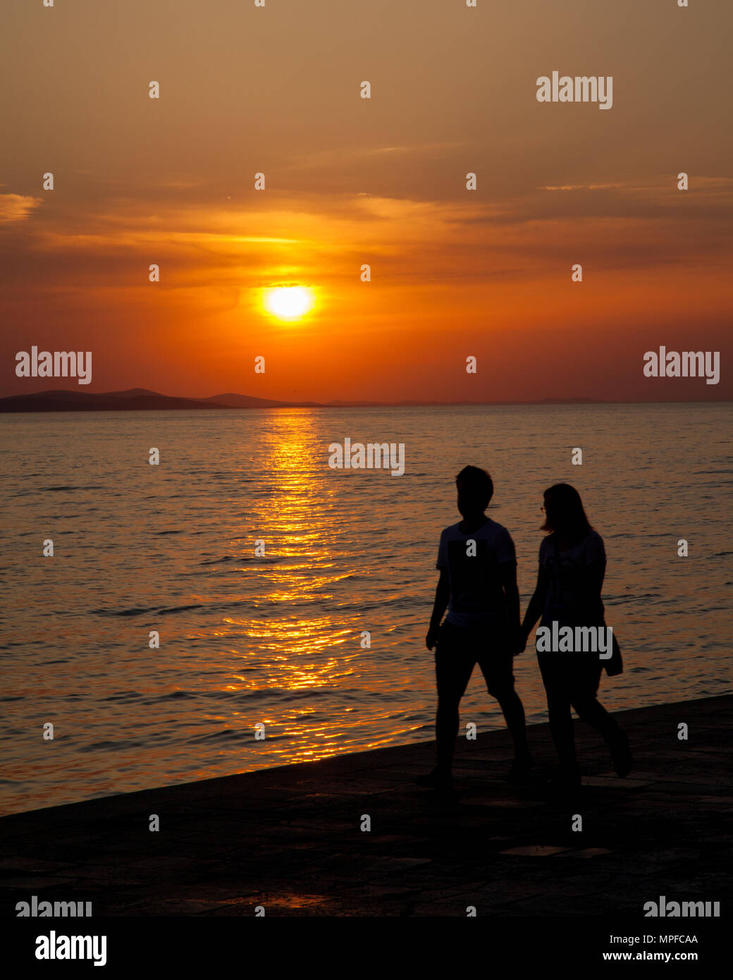 Man and woman watching beautiful glorious golden red and orange vivid vibrant sunset over the sea at the port of Zadar on the Adriatic coast Croatia - Stock Image