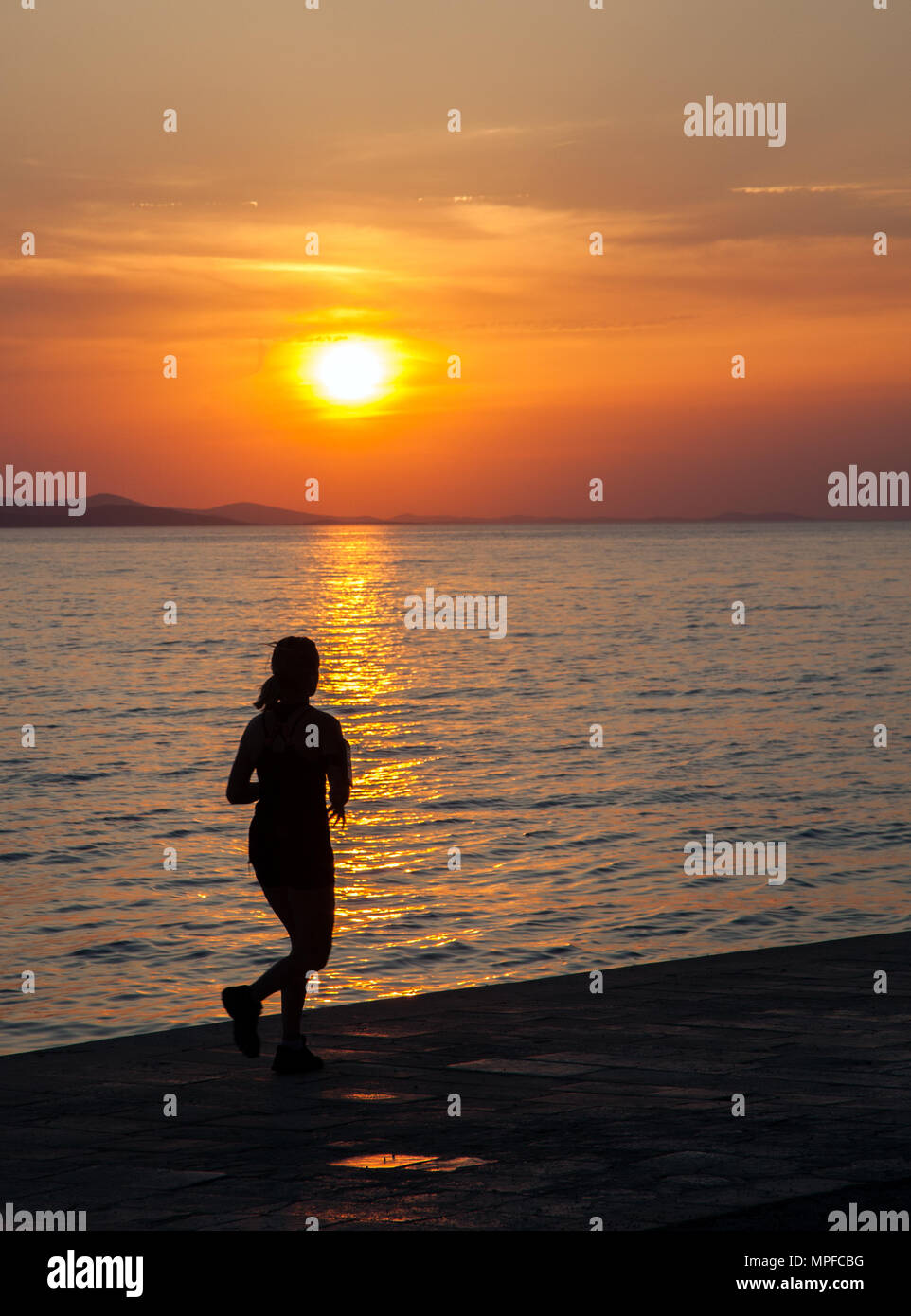 Girl running into the beautiful glorious golden red and orange vivid vibrant sunset over the sea at the port of Zadar on the Adriatic coast Croatia - Stock Image