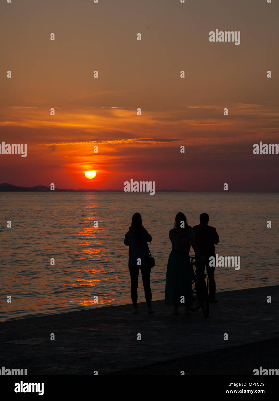 People watching beautiful glorious golden red and orange vivid vibrant sunset over the sea at the port of Zadar on the Adriatic coast Croatia - Stock Image