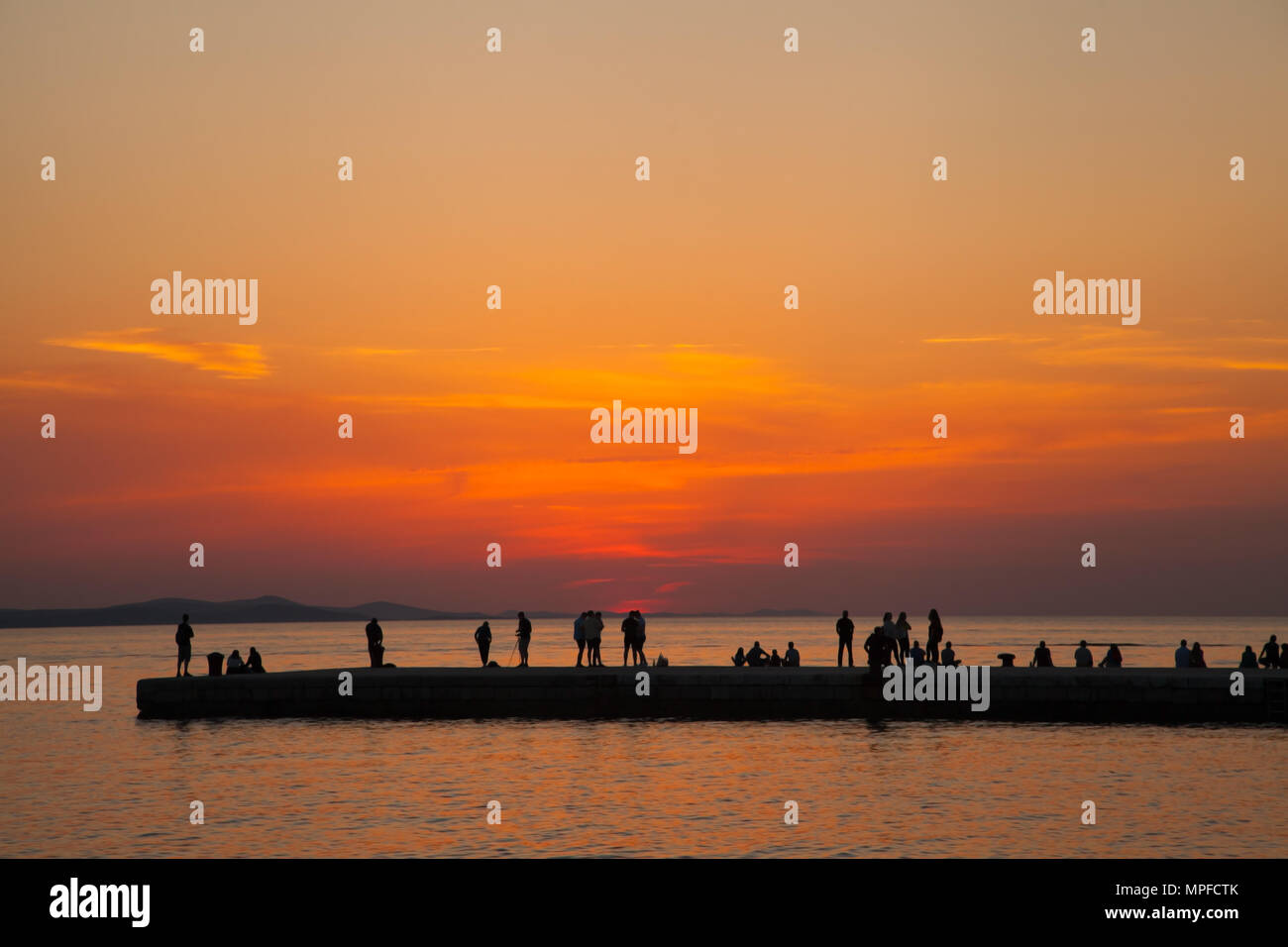 People watching beautiful glorious golden red and orange vivid vibrant sunset from the pier over the sea at the Adriatic port of Zadar Croatia - Stock Image