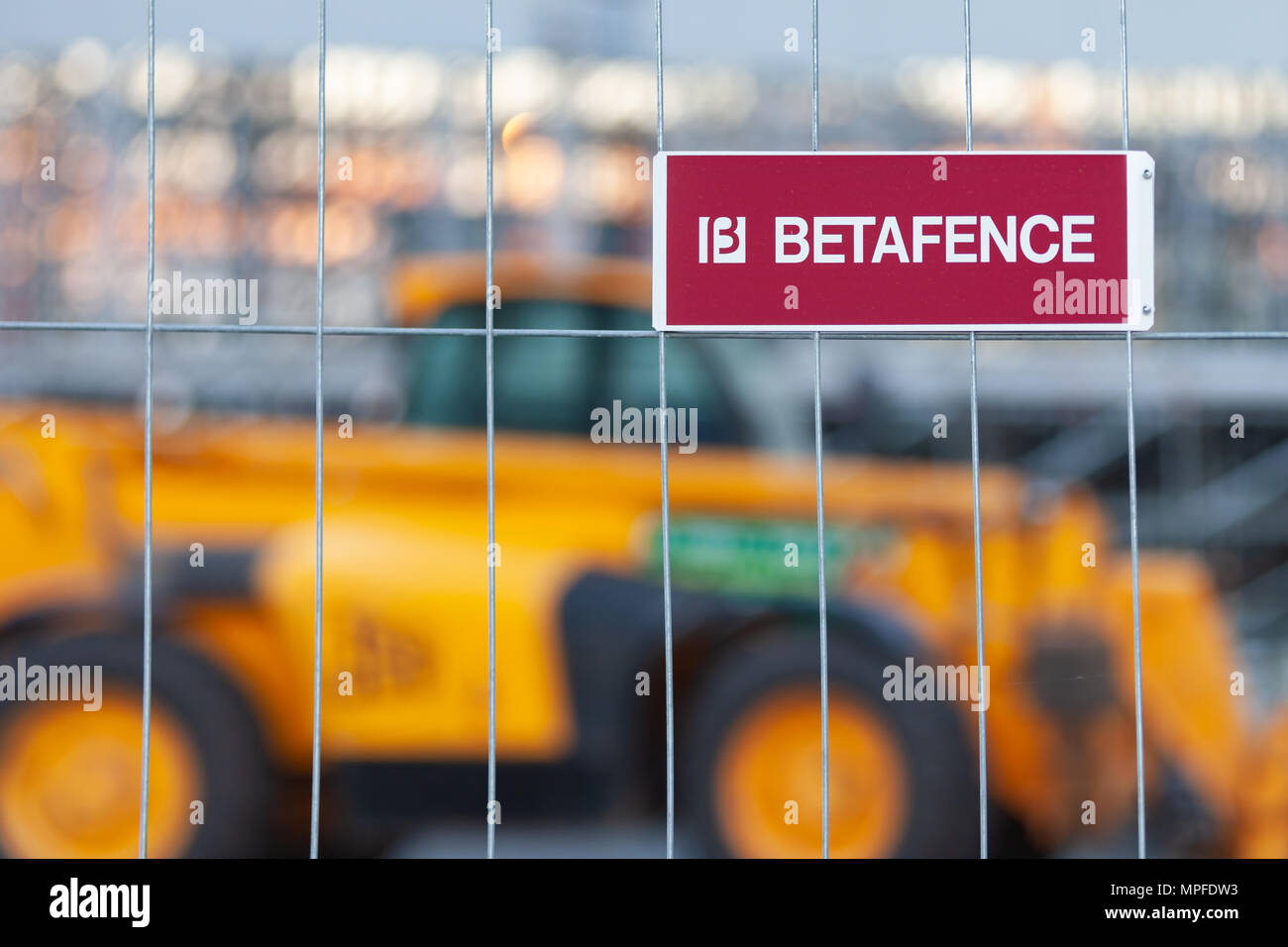 MOSCOW, RUSSIA - May 21, 2018: A plate of burgundy color with a white inscription fixed on a metal grid. Logotype: 'BETAFENCE'. Behind the fence in th - Stock Image