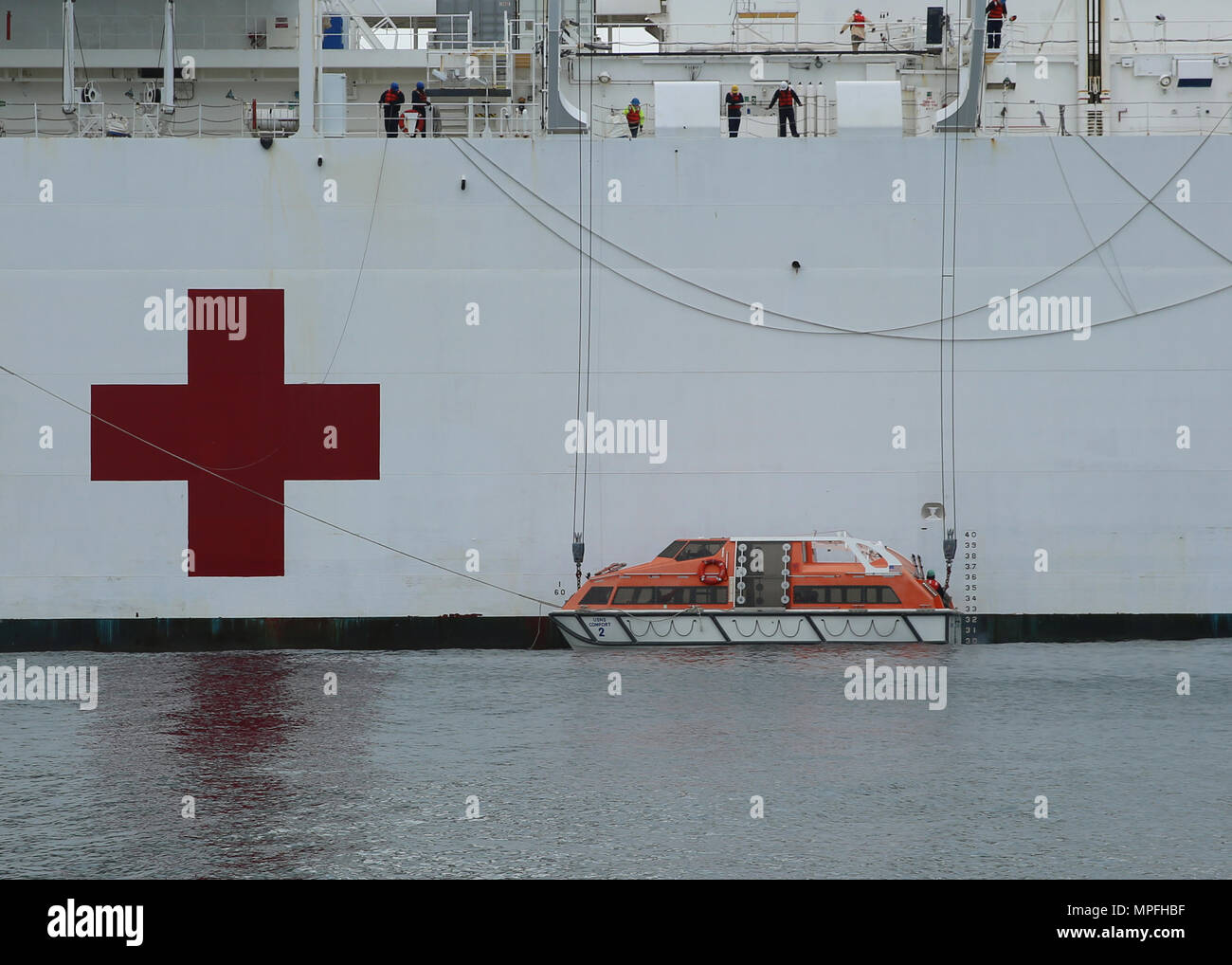170223-N-OH262-759 ATLANTIC OCEAN (Feb. 23, 2017) Civil service mariners assigned to the Military Sealift Command hospital ship USNS Comfort's (T-AH 20) lower the vessel's tender into the water. Comfort's underway period was part of the 2017 Comfort Exercise (COMFEX). The exercise is a quarterly training battery designed to keep the medical personnel, support staff and civil service mariners who serve aboard the ship proficient in their duties. Comfort provides an afloat, mobile, acute surgical medical facility when called upon to the U.S. military, and hospital services to support U.S. disast - Stock Image