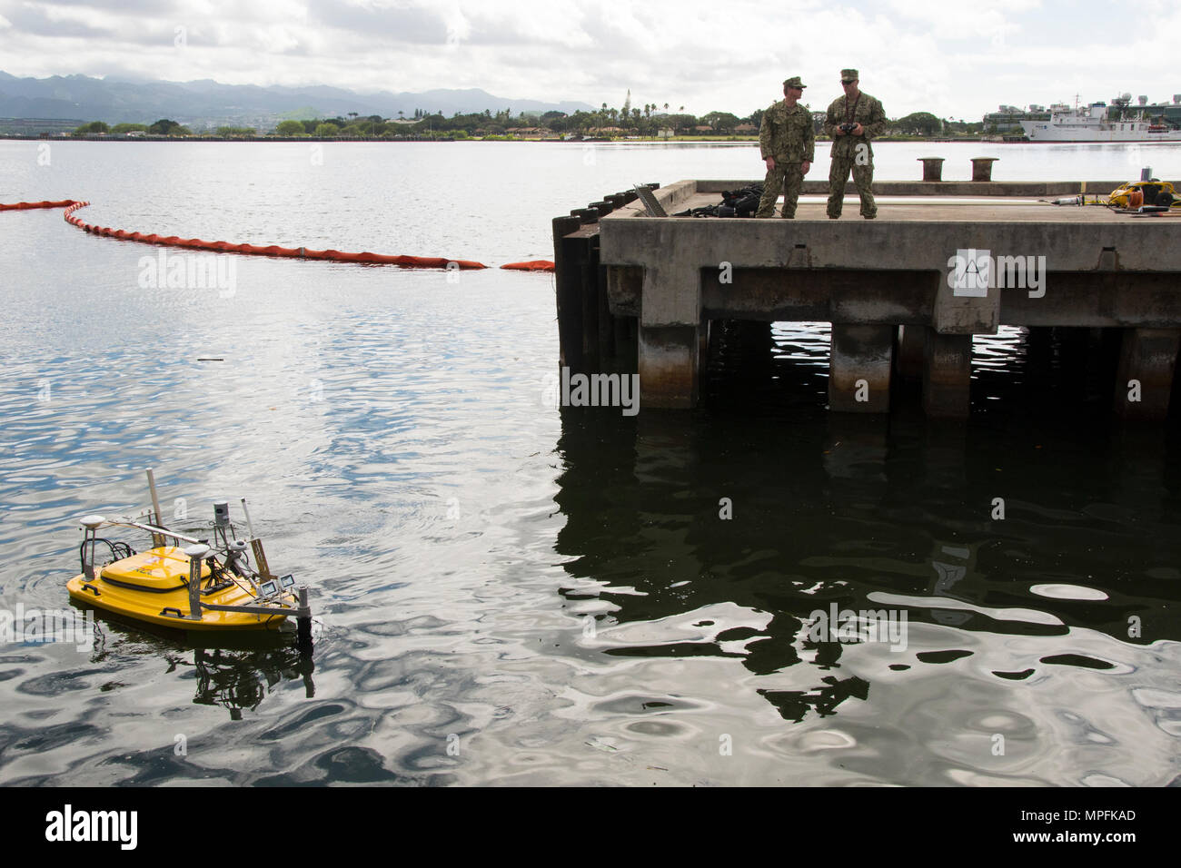 Navy underwater construction team members demonstrate the capabilities of a Multifunctional Assessment Reconnaissance Vehicle (MARV) to capture detailed engineering survey data.  Army and Navy divers assigned to engineer units partnered for a technology demonstration at Pearl Harbor Victor Pier 3, March 3, 2017. The MARV is a remote operated vehicle equipped with sensors and cameras, used for collecting data to identify damaged areas beneath the pier. Stock Photo