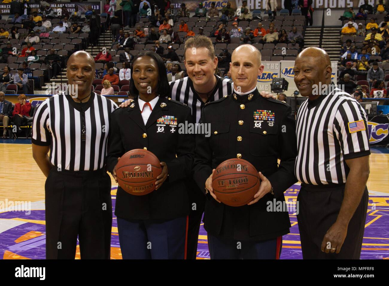 Major Charles Miller (right) and Lt. Col. Melanie Bell-Carter (left) pose for a photo with referees before tip-off at the Scope Arena in Norfolk, Virginia on March 9, 2017. The Marines were brought out to the center of the court to receive recognition for Hoops for Troops Night. The Marine Corps acknowledges this event as a valuable opportunity to spread public awareness of the Marine Corps and reinforce the idea of the armed serves as a career option within the African American community. Miller currently serves as the commanding officer of recruiting station Richmond and Bell-Carter currentl - Stock Image