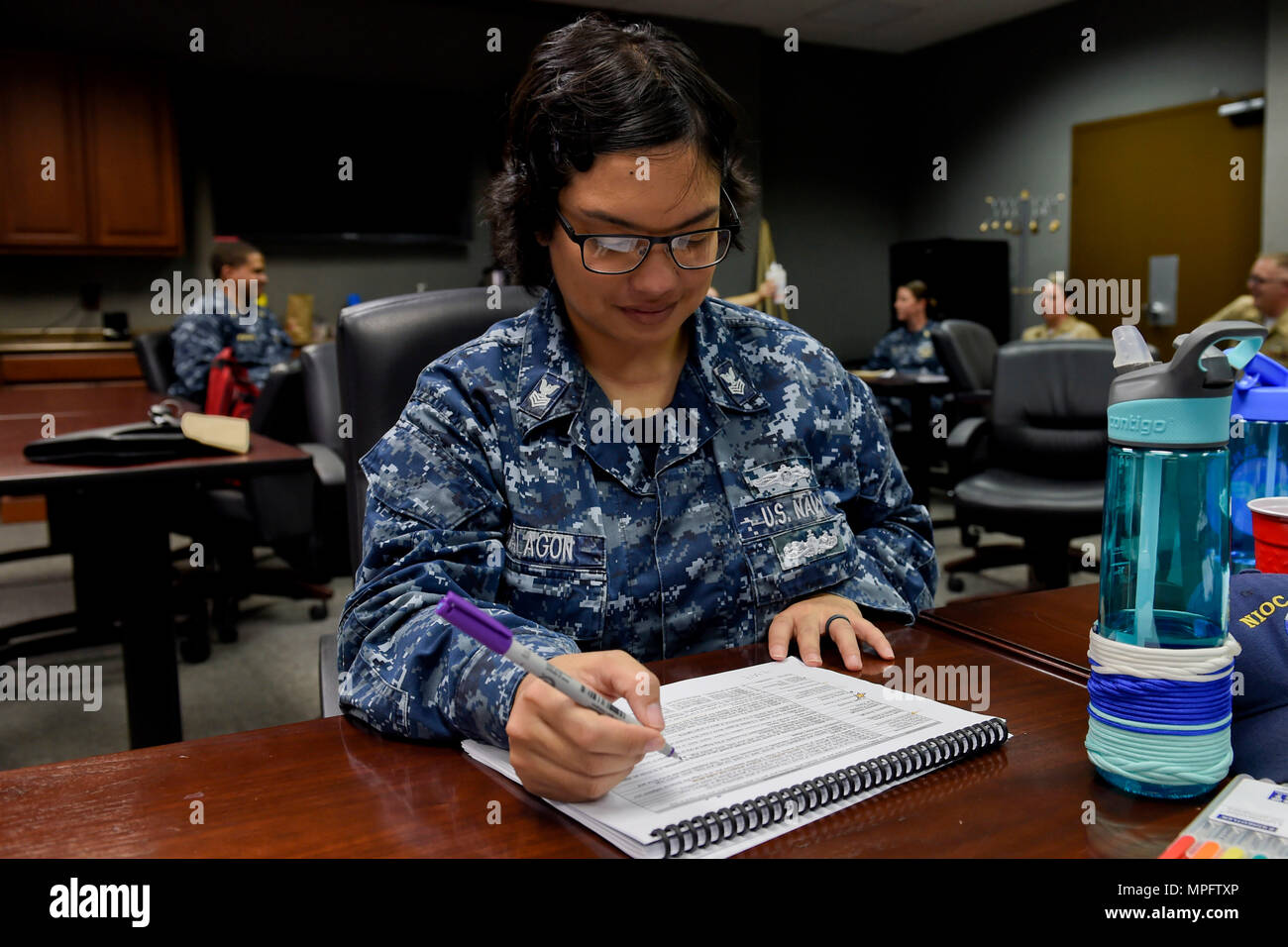 170309-N-FI568-035  PENSACOLA, Fla. (March 9, 2017) Cryptologic Technician (Interpretive)(CTI) 1st Class Amorita Malogon takes notes during a biennial occupational standards review for the CTI rating. The occupational standards review process breaks down core tasks, job descriptions, and skills and abilities for each rating. It serves as the basis for all Navy professional development and training tools, such as rate training manuals, personal qualification standards, course curricula and advancement exams. (U.S. Navy photo by Mass Communication Specialist 2nd Class Taylor L. Jackson/Released) - Stock Image