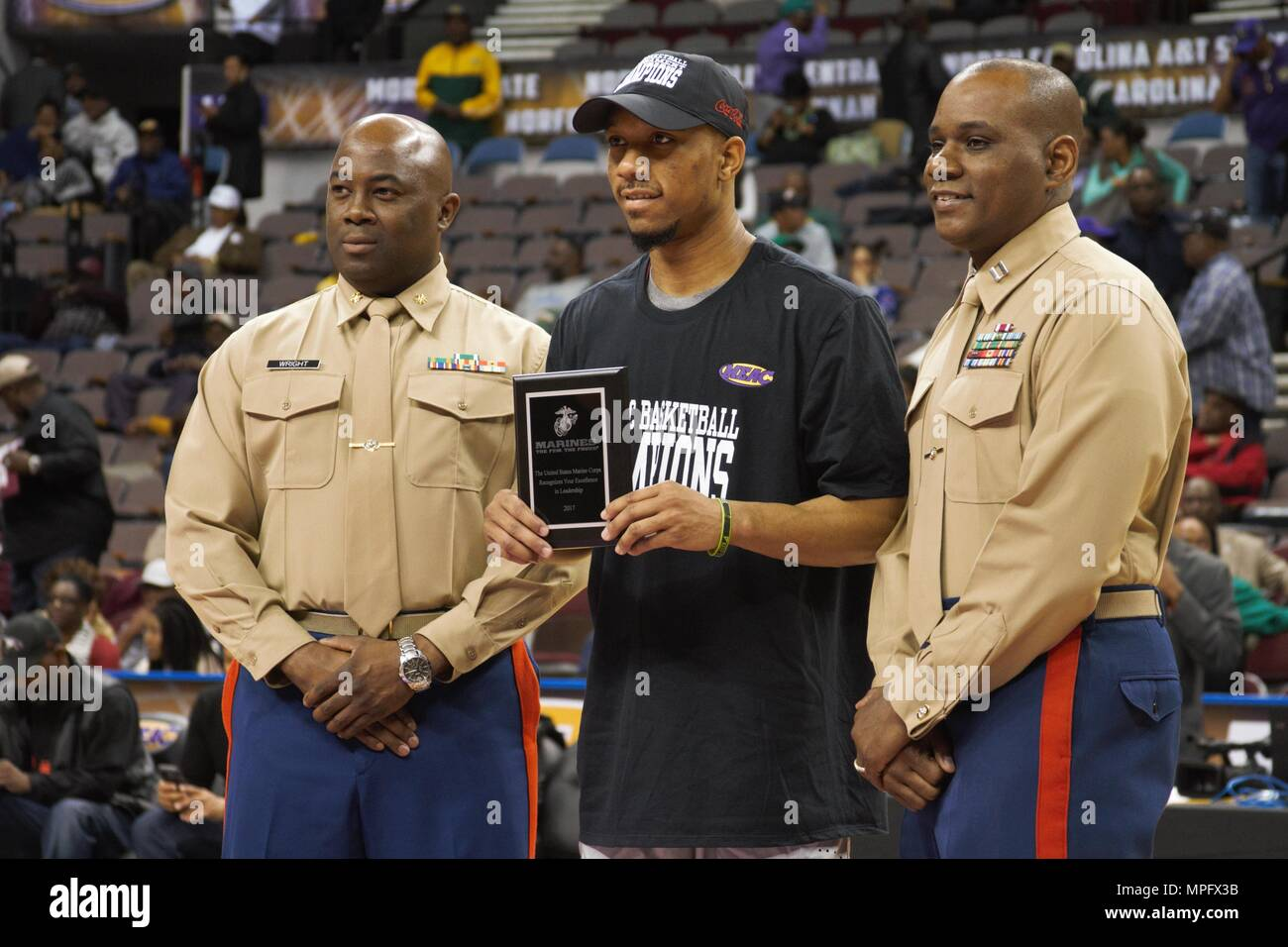 Marines pose for a picture with Rashaun Madison of North Carolina Central University at the Scope Arena in Norfolk, Va., March 11, 2017. The Eagles won the MEAC tournament and earned an automatic bid into the NCAA tournament. The Marine Corps is proud to recognize and celebrate those young people who display the qualities of a leader through their commitment to hard work in school, as well as in their extracurricular activities. - Stock Image