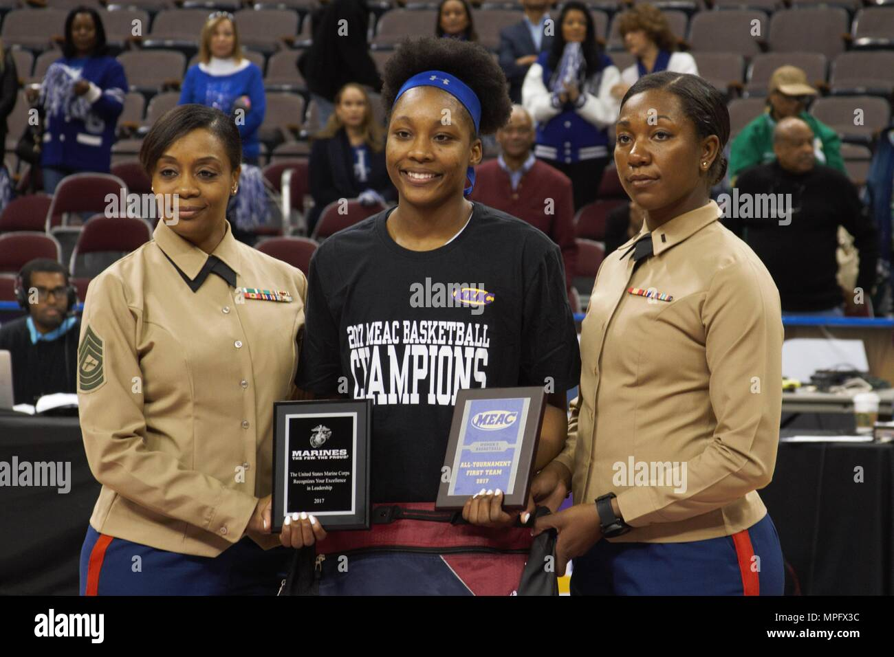 Marines pose for a picture with Monnazjea Finney-Smith of Hampton at the Scope Arena in Norfolk, Va., March 3, 2017. The Pirates won the MEAC tournament and earned an automatic bid into the NCAA tournament. The Marine Corps is proud to recognize and celebrate those young people who display the qualities of a leader through their commitment to hard work in school, as well as in their extracurricular activities. Stock Photo