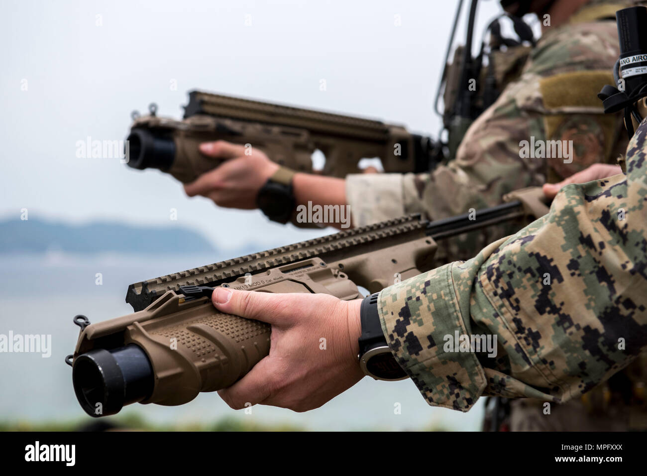 A U.S. Air Force combat controller from the 320th Special Tactics Squadron, and a Marine joint terminal attack controller from the 5th Air Naval Gunfire Liaison Company, III Marine Expeditionary Force, wield 40 mm grenade launchers during a training exercise March 10, 2017, at the Irisuna Jima Training Range, Okinawa, Japan. The launchers are used to shoot out smoke grenades as a visual marker for friendly aircraft. (U.S. Air Force photo by Senior Airman John Linzmeier) - Stock Image