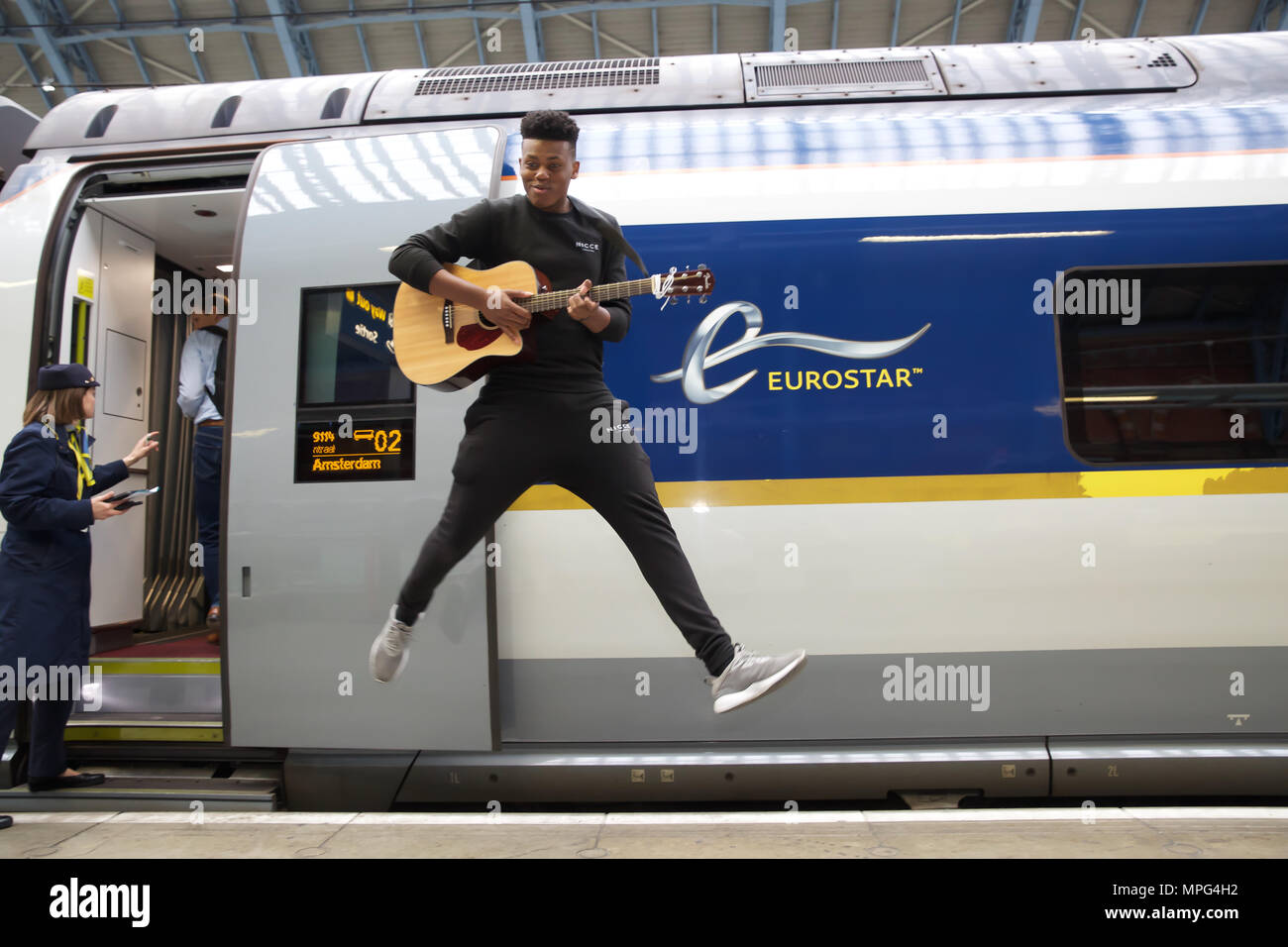 St Pancras, UK. 23rd May 2018. Ky Lewis, Winner of Gigs Eurostar prize jumps for joy before he boards the train to Amsterdam. He set off on a whirlwind busking tour of Amsterdam. He will serenade passengers on the train as they travel under the Channel and complete the day busking in Amsterdam.Credit Keith Larby/Alamy Live News - Stock Image