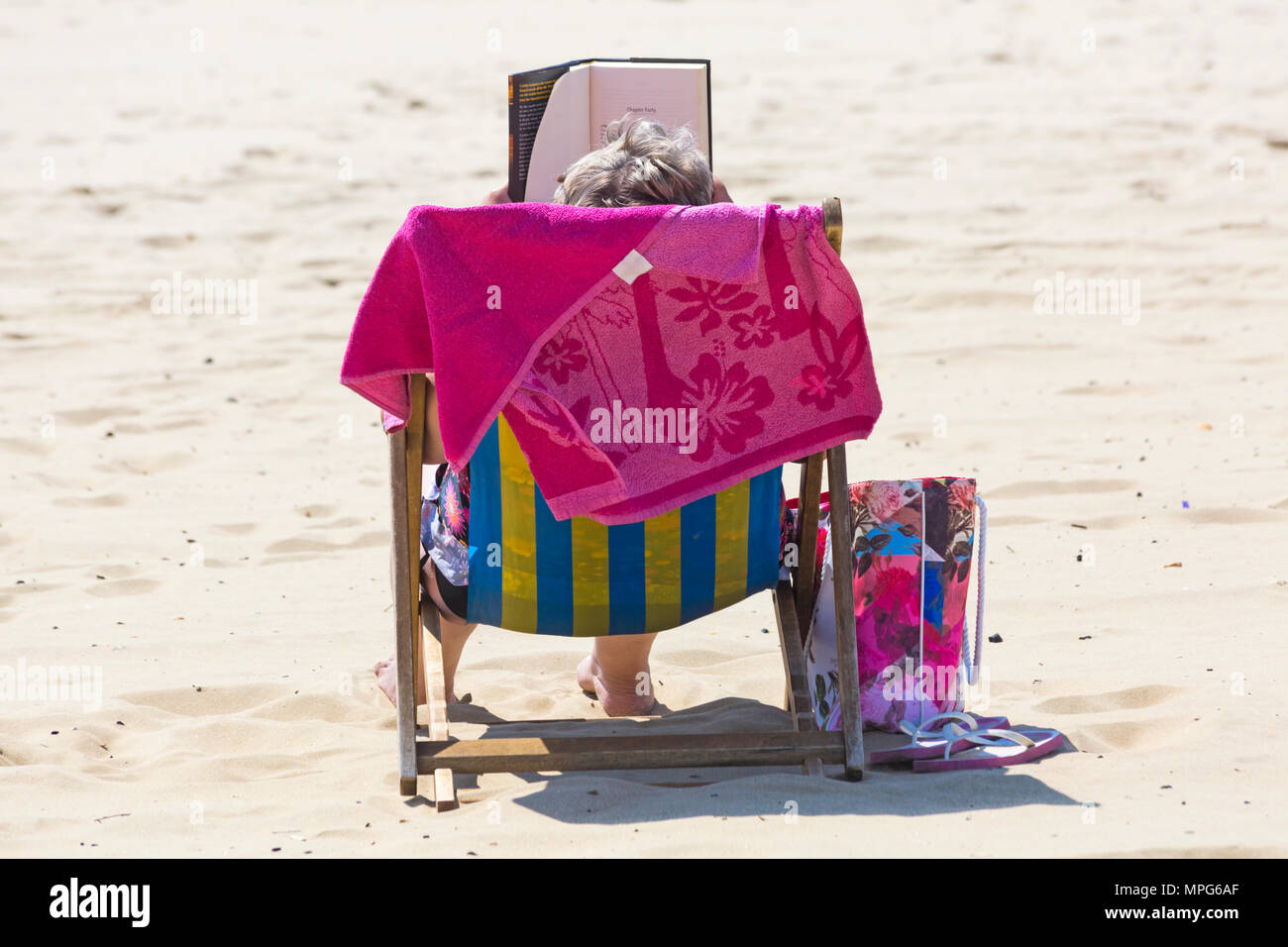 Bournemouth, Dorset, UK. 23rd May 2018. UK weather: lovely warm sunny day with unbroken sunshine, as visitors head to the beach. Woman reading book in deckchair - back view. Credit: Carolyn Jenkins/Alamy Live News - Stock Image