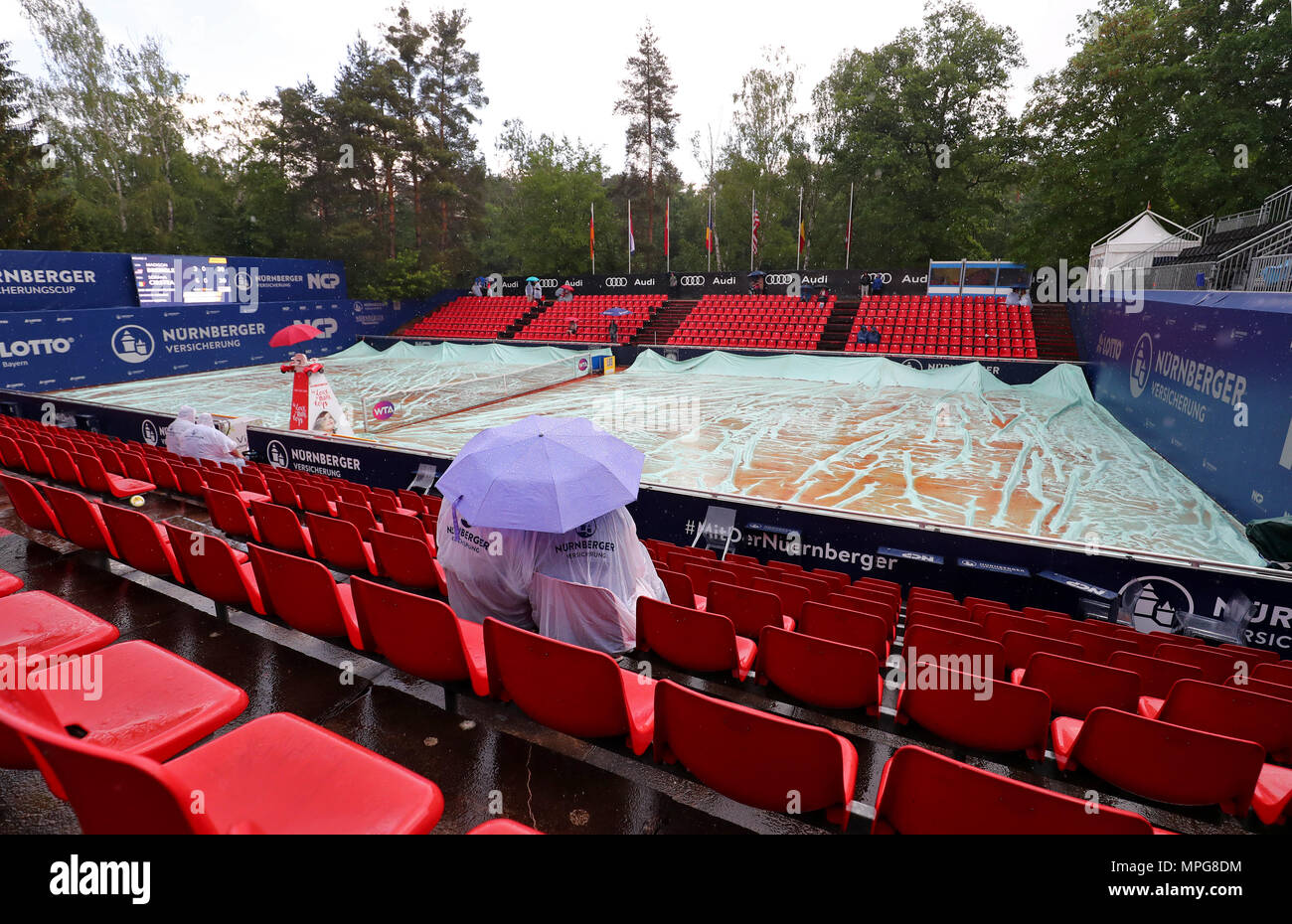 23 May 2018, Germany, Nuremberg: Tennis, WTA-Tour, women's singles. Two visitors sitting in the stands with rain ponchos and umbrellas during a rain interruption. Photo: Daniel Karmann/dpa - Stock Image