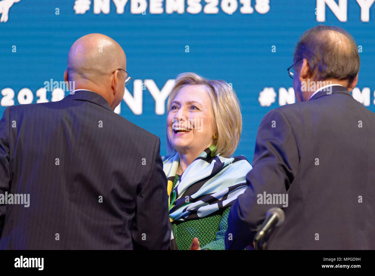 Hempstead, New York, USA. 23rd May, 2018. HILLARY CLINTON greets GEOFF BERMAN, Executive Director of New York State Democratic Committee, as she goes on stage to deliver Keynote Address during Day 1 of New York State Democratic Convention, held at Hofstra University on Long Island. Clinton, the former First Lady and NYS Senator, endorsed the re-election of Gov. A. Cuomo for a third term, and mentioned how Hofstra was the site of her first 2016 debate with Trump. Credit: Ann Parry/ZUMA Wire/Alamy Live News - Stock Image