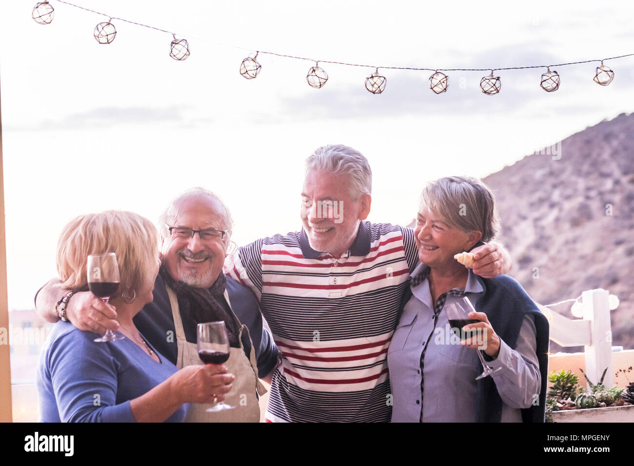 group of 4 seniors, two couples, stay togheter and have fun enjoing a cup of wine outdoor in the rooftop. vacation elderly concept and friendship. sun - Stock Image