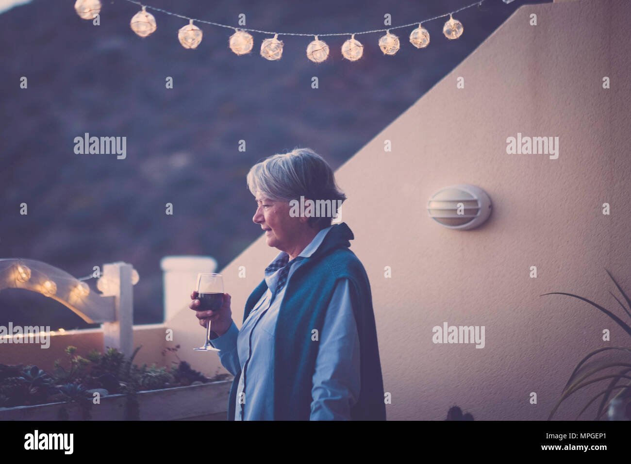 aged senior woman drink some wine during a celebration event by night in vacation. summer style and mountains nature view. beautiful adult model lifes - Stock Image
