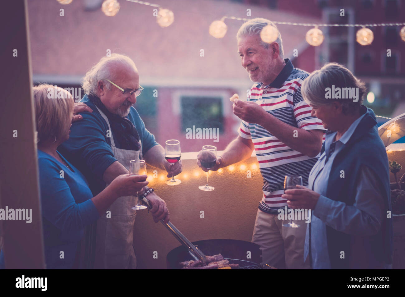barbeque bbq and some wine to celebrate an event. group of adult people enjoy lifestyle outdoor in the terrace with city view. eat meal and drink wine - Stock Image