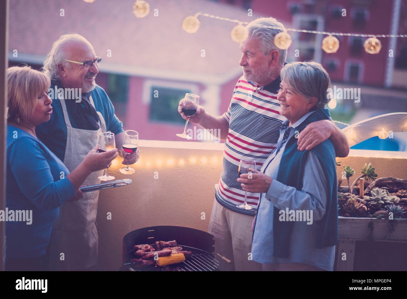 group of friends seniors having a bbq barbeque together on the rooftop with beautiful view on other buildings. Bulb lights in the terrace and smile ha - Stock Image
