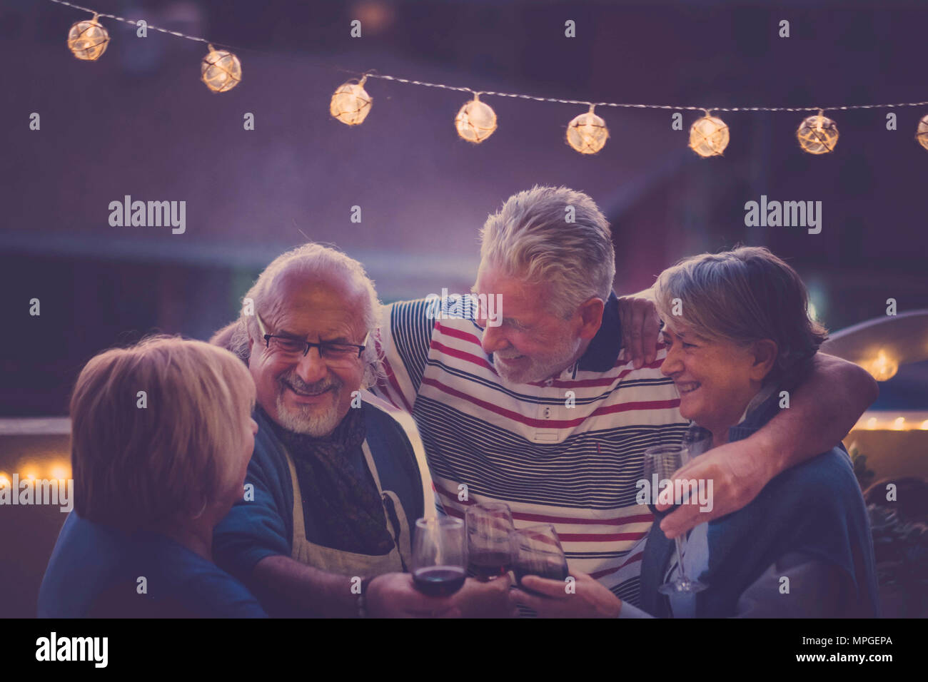 Focus on the man. group of senior adult aged doing party night on the rooftop at home. everybody hug together and smile and laugh for a nice activity  - Stock Image