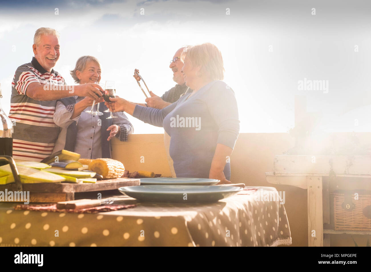 group of senior people doing party and barbeque outdoor at the terrace rooftop. celebration and event time at the sunset. happiness and nice lifestyle - Stock Image