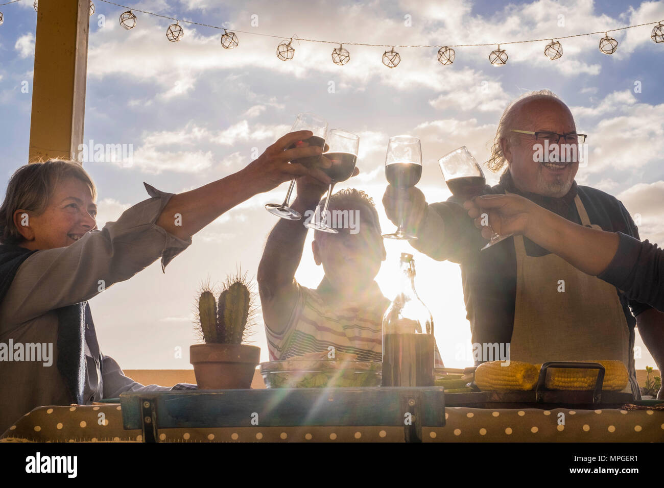 happy group of adults celebrate an event with cups of wine outdoor in the terrace with sunset and backlight. golden tones for happiness lifestyle conc - Stock Image