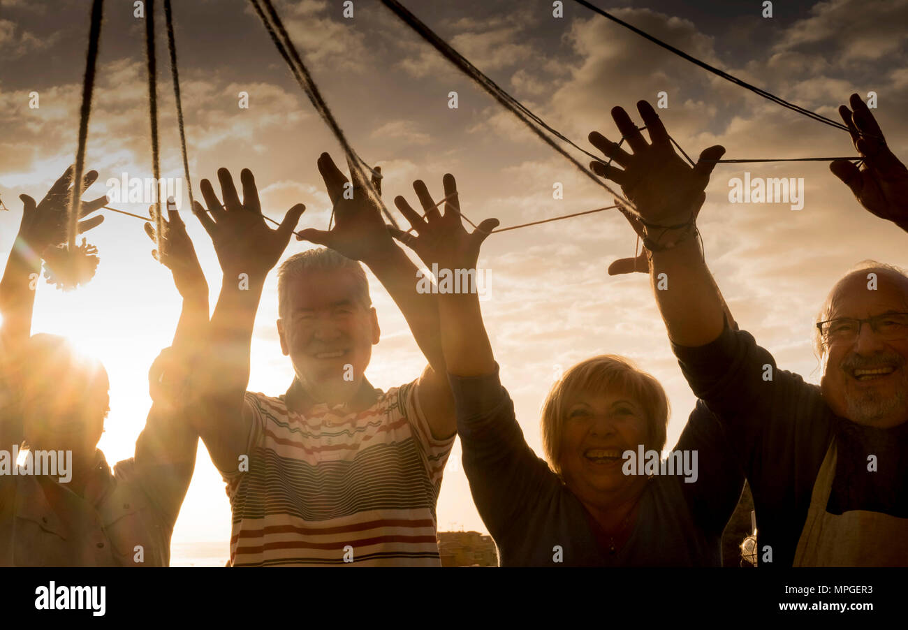 work and have fun together outdoor concept. leisure activity during dinner in the evening with sunset in background. happy day of vacation for senior  - Stock Image