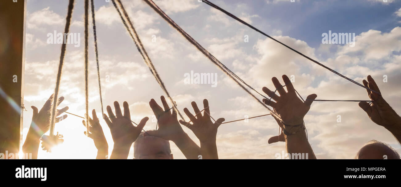 teamwork of elderly people group with a lot of hands united between a cord under the sunlight. all hands together with beautiful sky on the background - Stock Image